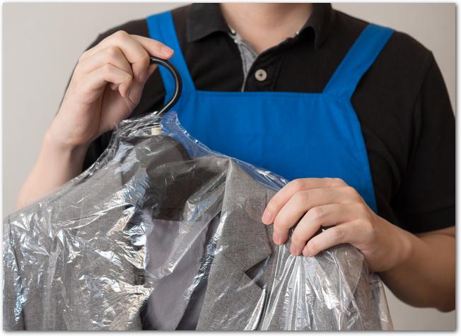 スーツを持つクリーニング店の店員の手元