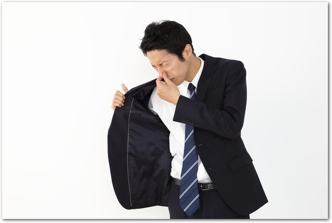 スーツの脇の部分の臭いに鼻を押さえるサラリーマン