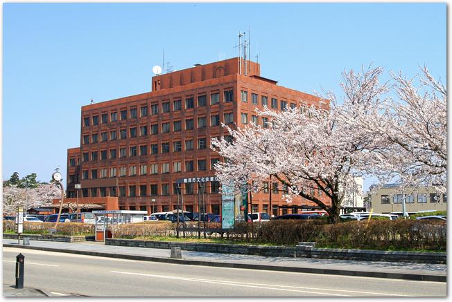桜の時期の鶴岡市役所の外観