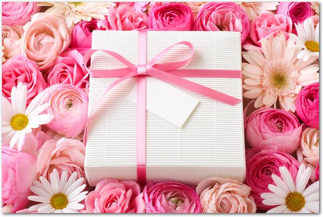 ピンク系の花に囲まれた母の日のプレゼント