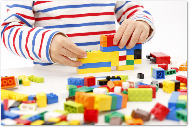 白いテーブルの上でレゴを組み立てて遊ぶ男の子の様子
