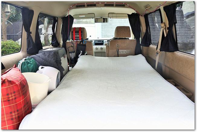 マットを敷いて車中泊の準備がされたミニバンの車内の様子