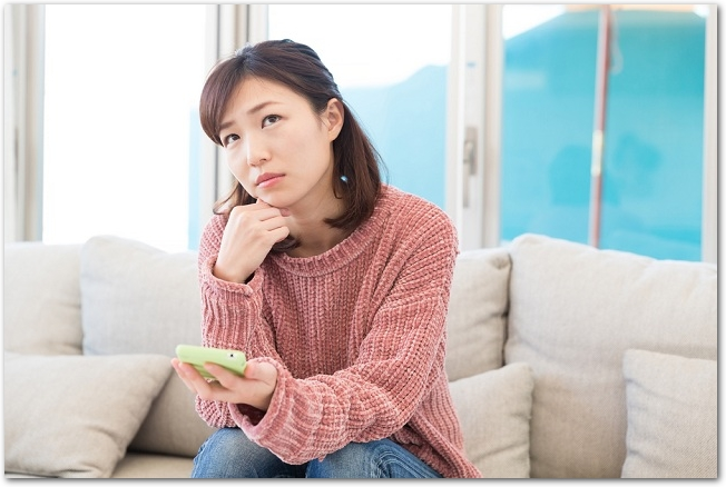 ソファーに座ってスマホ片手に悩む女性の様子