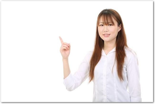指をさす笑顔の若い女性の様子