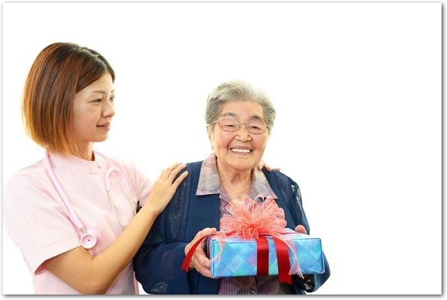 プレゼントを持つシニア女性と傍で支える女性介護士