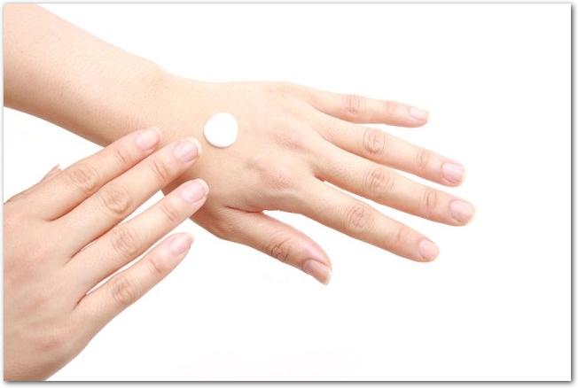左手の甲にクリームを塗っている女性の手