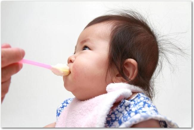 離乳食を食べている女の子の赤ちゃんの様子