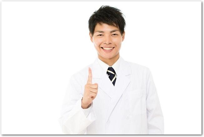 指を指す笑顔の男性医師の様子