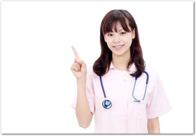 指をさす若い女性看護師の様子