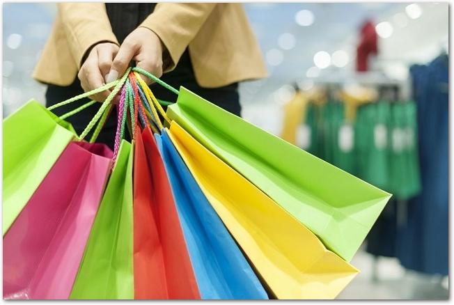 カラフルなショッピングバッグをたくさん持っている女性の手元