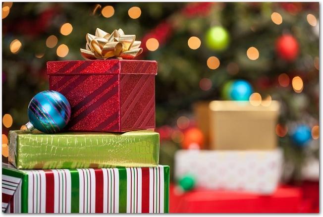 ぼやけたクリスマスツリーの前に置かれたプレゼント