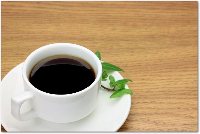 木のテーブルに置かれた白いカップにコーヒーが入っている様子