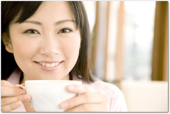 白いコーヒーカップを持つ笑顔の女性の様子