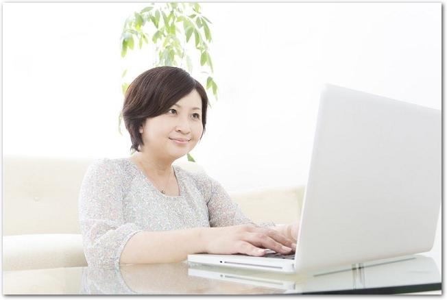 リビングのテーブルでノートパソコンを操作している女性の様子