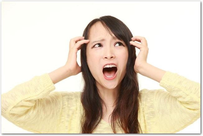 ショックを受けて頭を抱える女性の様子