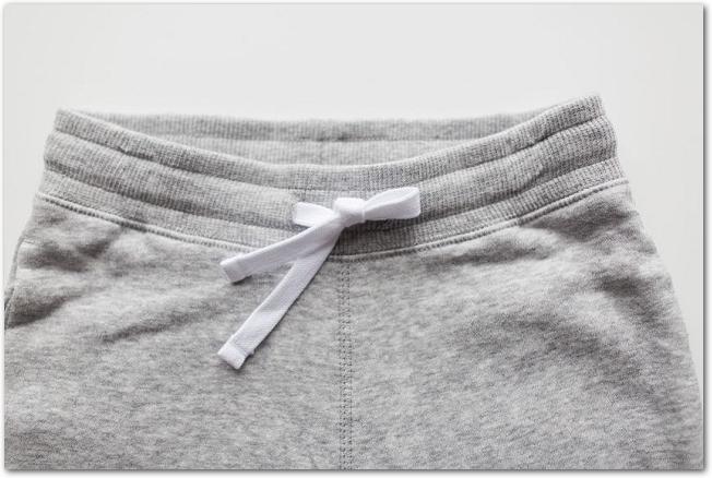 白背景に置かれたグレーのスウェットパンツ