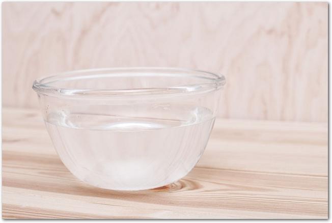 木のテーブルに置かれた水の入ったガラスのボウル