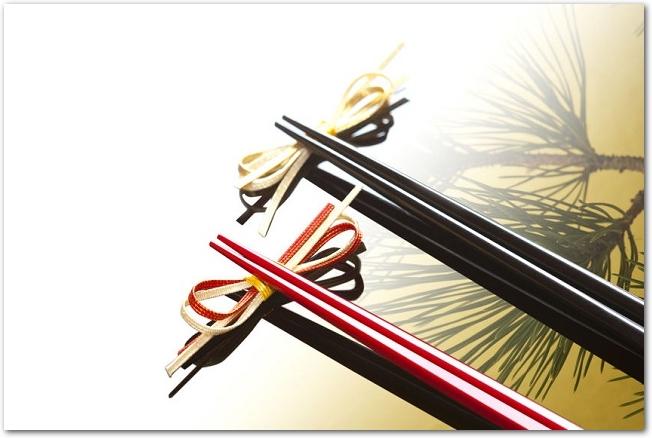 松葉の模様の上に置かれた黒と赤の箸と箸置き