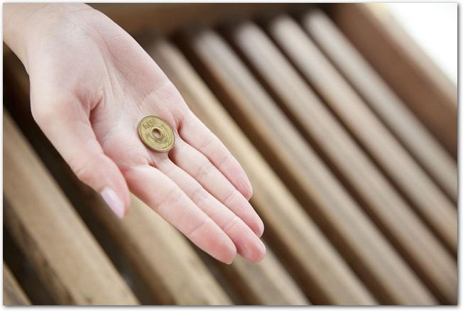 さい銭箱に五円玉を入れようとしている女性の手元の様子