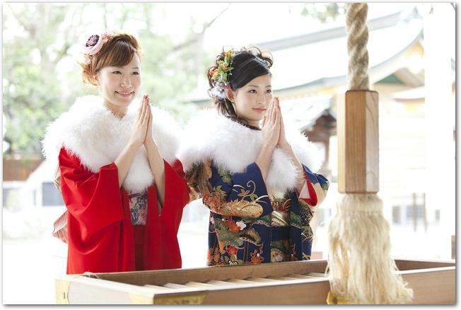 本殿の前で参拝する振袖姿の若い女性の様子
