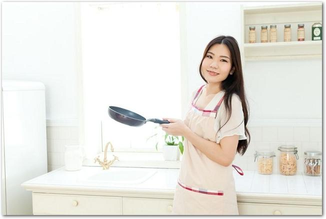 キッチンでフライパンを持つエプロン姿の笑顔の女性の様子