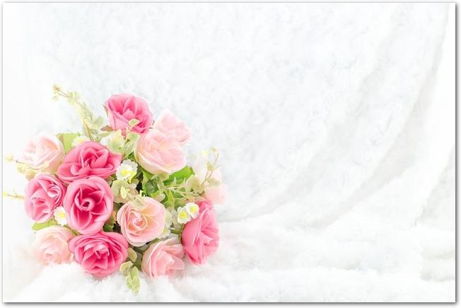白いファーの背景の上に置かれたピンクのウェディングブーケ
