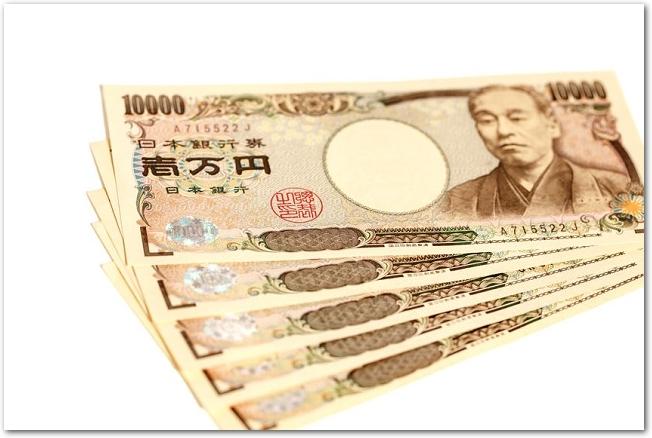 白背景に置かれた5枚の一万円札