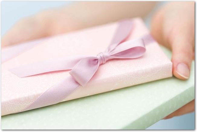 ピンク色と緑色のラッピングがされたプレゼントを持つ手元の様子