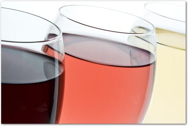 赤白とロゼ3つのワインが入ったグラスのアップ