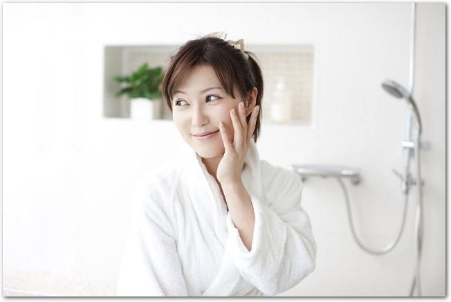 バスルームで頬に手を当てているバスローブ姿の笑顔の女性
