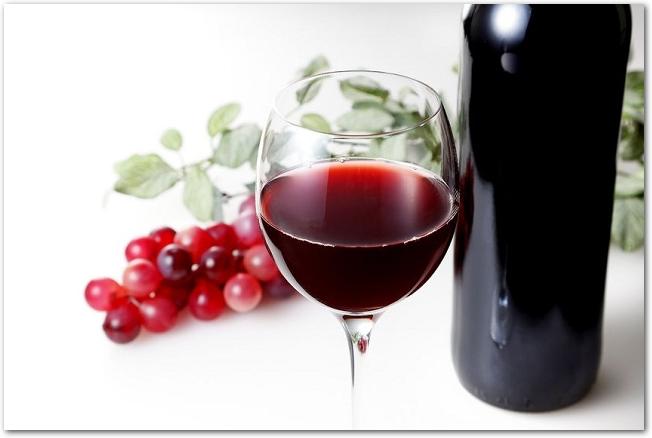 ブドウの前に置かれたワインボトルとグラスに注がれた赤ワイン