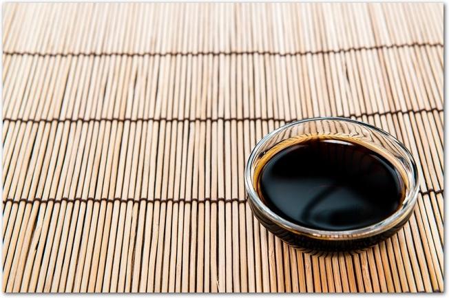 竹のランチョンマットにガラスの器に入っためんつゆが置かれている様子
