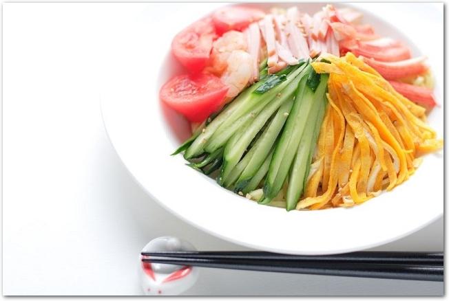 錦糸卵やハムなどの乗った冷し中華と箸
